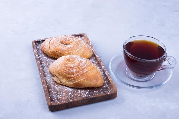 Eine tasse tee mit badamburas im teller auf weißem hölzernem hintergrund