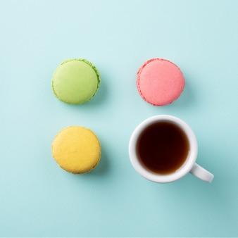 Eine tasse tee mit bunten macarons auf hellblauer oberfläche