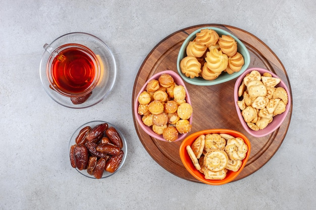 Eine tasse tee mit datteln neben einer auswahl von keksen auf einem holzbrett auf marmorhintergrund. hochwertiges foto