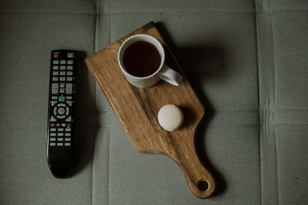 Eine tasse tee mit dessert und eine tv-fernbedienung auf der couch. zeit zu hause auszuruhen. tee trinken auf der couch vor dem fernseher. wochenende mit filmen und tee