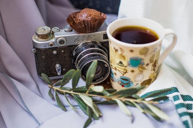 Eine tasse tee mit einer schokoladenpraline und einer fotokamera.