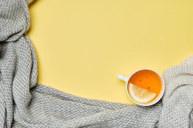Eine tasse tee mit einer zitrone und einem schal auf gelbem grund.