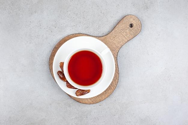 Eine tasse tee mit einigen datteln auf untertasse auf einem holzbrett, auf marmoroberfläche