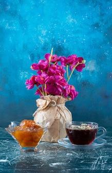 Eine tasse tee mit feigenkonfitüre in der untertasse.