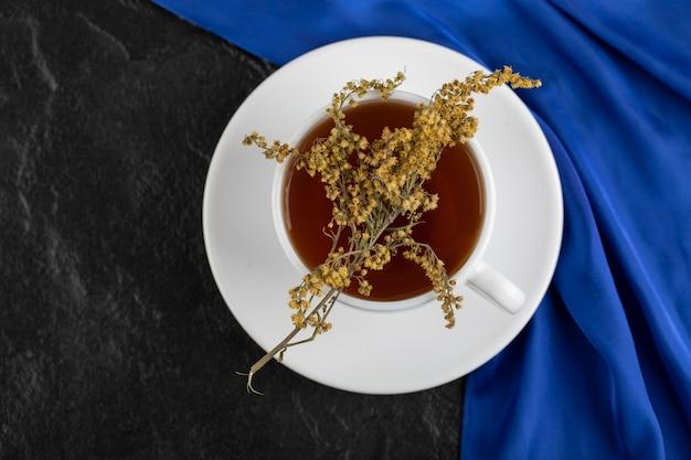 Eine tasse tee mit getrockneten blumen auf einem schwarzen tisch.