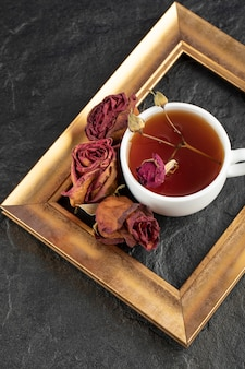 Eine tasse tee mit getrockneter rose und rahmen auf einem schwarzen tisch.