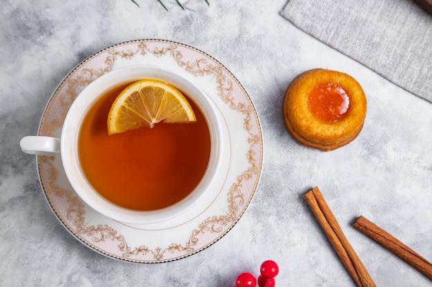 Eine tasse tee mit hausgemachtem aprikosenmarmeladen-fingerabdruck-keks. hochwertiges foto
