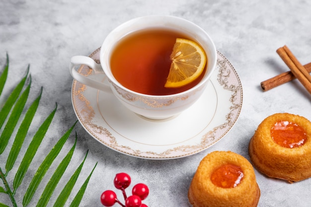 Eine tasse tee mit hausgemachtem aprikosenmarmeladen-fingerabdruck-keks.