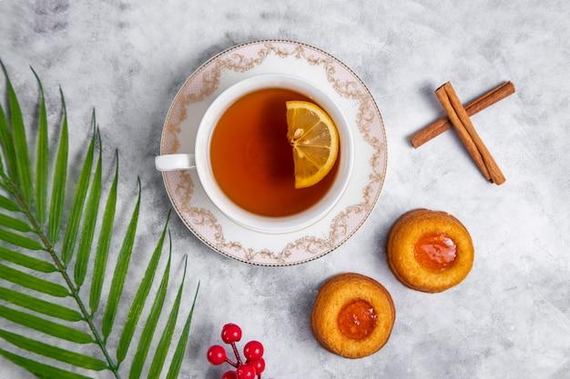 Eine tasse tee mit hausgemachten aprikosenmarmelade fingerabdruck kekse.