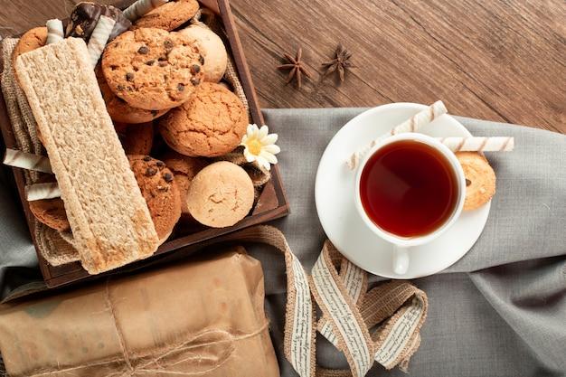 Eine tasse tee mit kekstablett herum. draufsicht