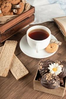 Eine tasse tee mit knusprigen crackern.