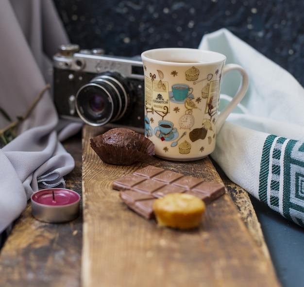 Eine tasse tee mit schokoriegel auf einem stück holz.