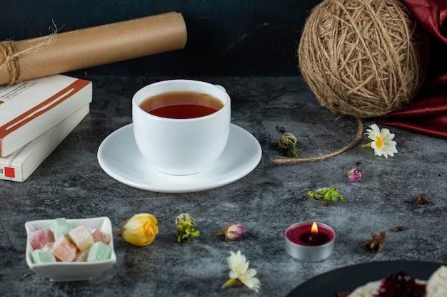 Eine tasse tee mit süßigkeiten und snacks