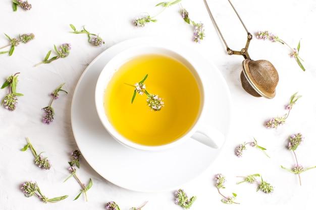 Eine tasse tee mit thymianblumen auf einem weißen hintergrund. der blick von oben. konzept der volksmedizin.