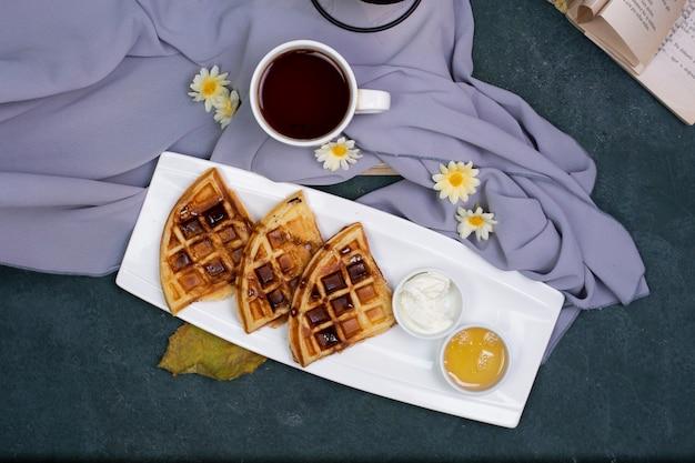 Eine tasse tee mit waffeln in der weißen platte.
