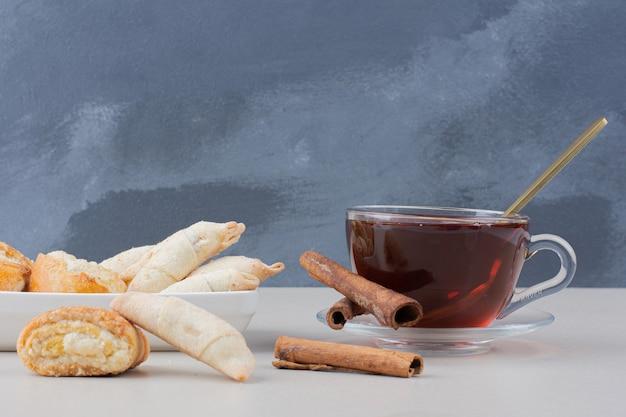 Eine tasse tee mit zimt und keksen auf weißem tisch.