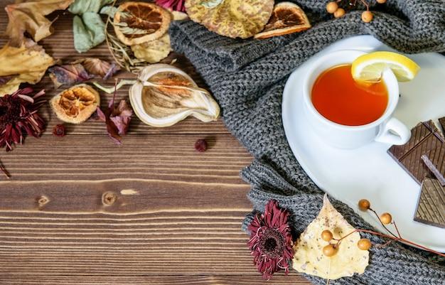 Eine tasse tee mit zitrone auf dem warmen winterpullover, trockene bunte blätter und blüten, blütenblätter auf dem holz