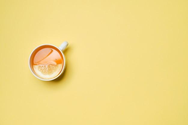 Eine tasse tee mit zitrone auf einem gelben papierhintergrund. draufsicht.