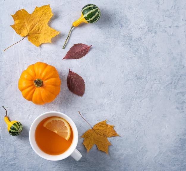 Eine tasse tee mit zitrone, dekorativem kürbis und etwas herbstlaub auf blau.