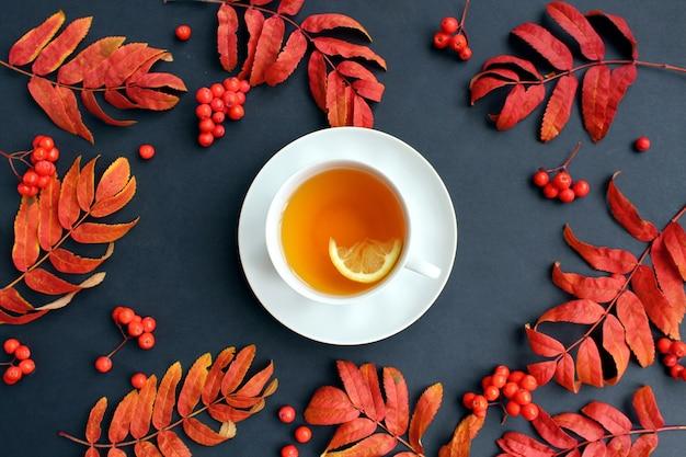 Eine tasse tee mit zitrone steht auf einer schwarzen oberfläche mit blütenblättern und ebereschenbeeren.