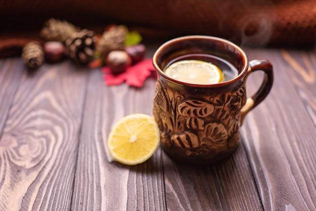 Eine tasse tee mit zitrone und zimtstangen auf einem holztisch warm gestrickte snood herbststimmung