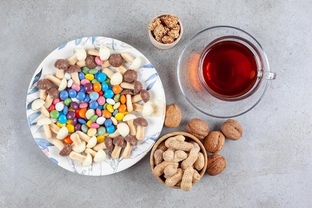 Eine tasse tee neben einer auswahl an süßigkeiten und nüssen auf marmorhintergrund. hochwertiges foto