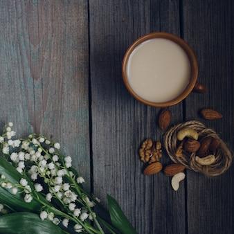 Eine tasse tee, nüsse, blumenstrauß von lilien auf einem hölzernen hintergrund