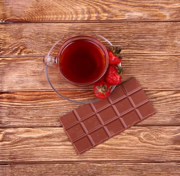 Eine tasse tee oder kaffee. dunkle schokolade. hölzerner hintergrund.