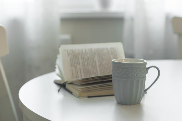 Eine tasse tee oder kaffee und ein offenes buch auf einer weißen tabelle. das konzept von gemütlichkeit, gemütlichkeit und wohnkomfort