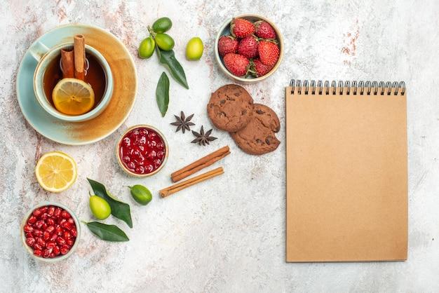 Eine tasse tee schalen mit beeren zitrusfrüchte sternanis und zimtstangen schokoladenkekse neben dem sahnenotizbuch die tasse tee mit zimt auf dem tisch