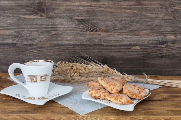 Eine tasse tee, selbst gemachte kekse und weizenähren auf einem hintergrund von hölzernen brettern.
