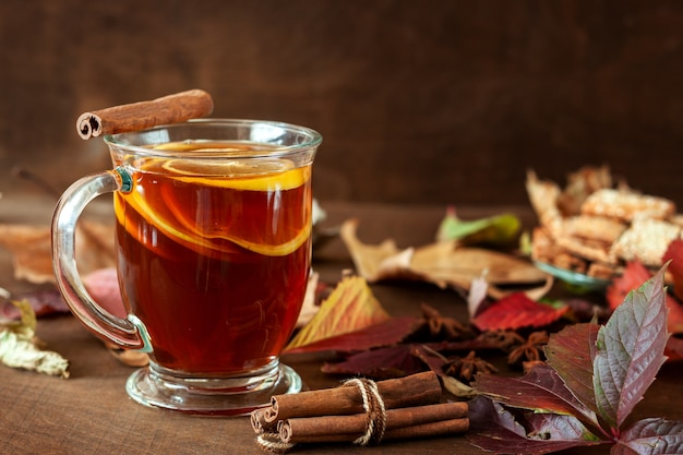 Eine tasse tee steht auf einem mit herbstlaub übersäten tisch