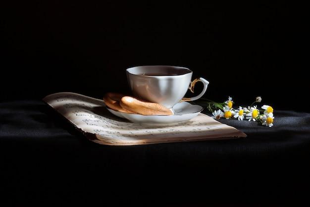 Eine tasse tee steht auf noten, backen auf einem teller und kamille