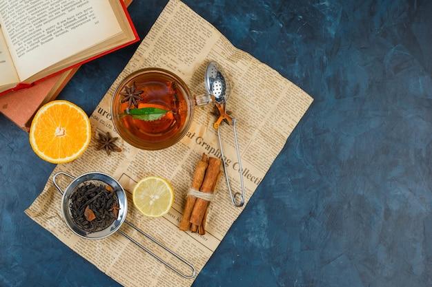 Eine tasse tee, teesiebe, zimt und orange mit zeitung und einem buch