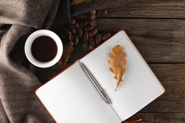 Eine tasse tee, umgeben von blättern, schokolade und einem buch. getönten foto. von oben betrachten