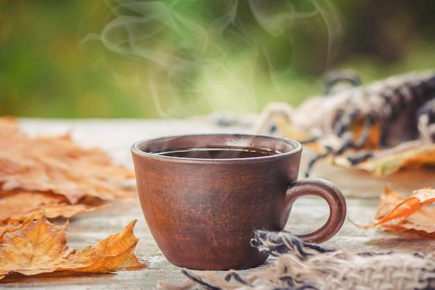Eine tasse tee und ein gemütlicher herbsthintergrund. selektiver fokus