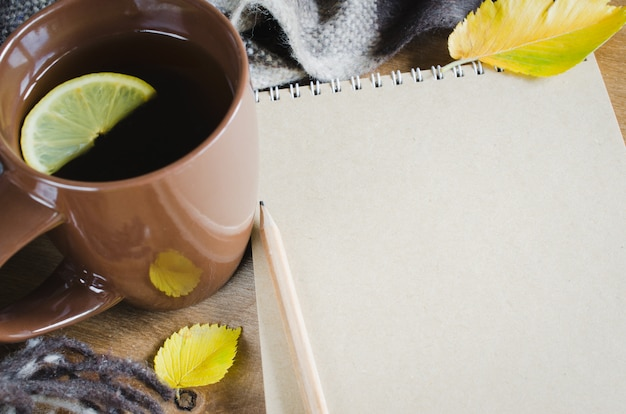 Eine tasse tee und ein leeres notizbuch für skizze.