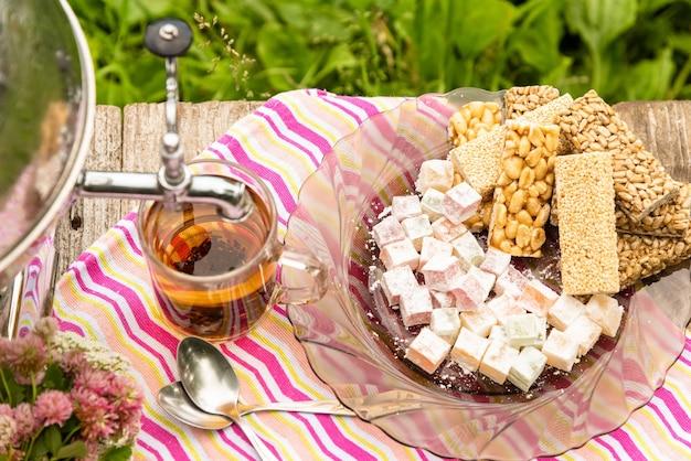 Eine tasse tee und ein samowar auf einem holztisch mit süßigkeiten.