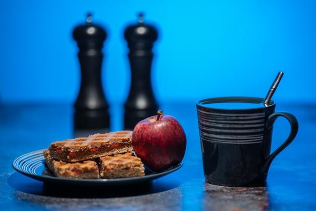 Eine tasse tee und ein teller mit keksen und apfel stehen auf dem tisch Premium Fotos