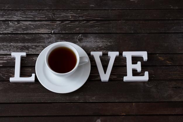 Eine tasse tee und ein wort der liebe aus weißen holzbuchstaben