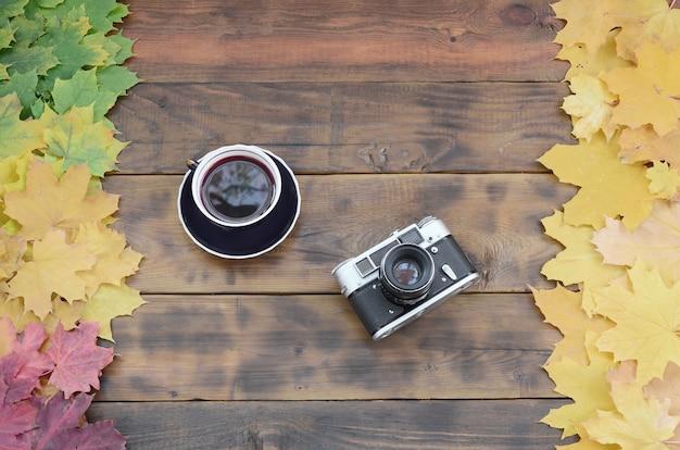 Eine tasse tee und eine alte kamera unter einem satz gelb gefallenen herbstlaubs