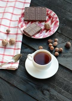 Eine tasse tee und eine tafel bitterschokolade. ansicht von oben.