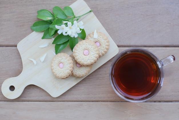 Eine tasse tee und kekse auf dem hölzernen behälter mit weißen blumen