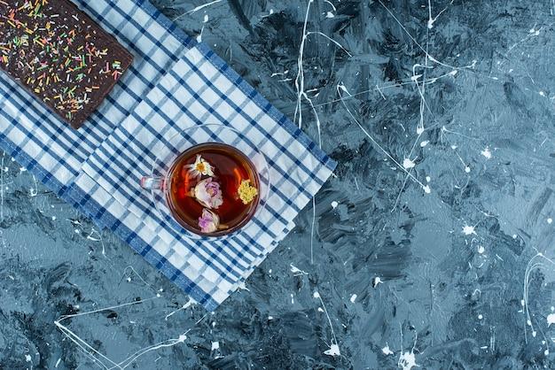Eine tasse tee und schokoladenwaffel auf geschirrtuch, auf dem blauen tisch.