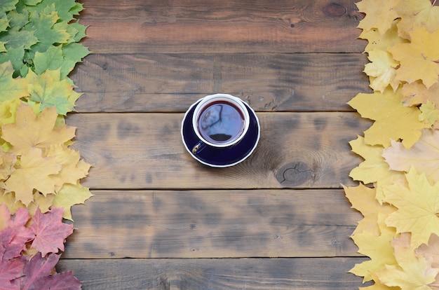 Eine tasse tee unter einem satz gelb färbendem gefallenem herbstlaub auf einem hintergrund