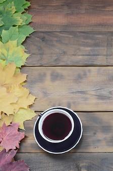 Eine tasse tee unter einem satz gelb färbendem gefallenem herbstlaub