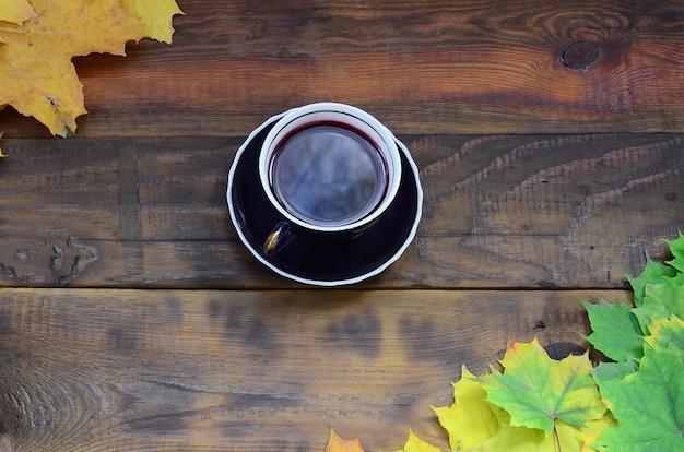 Eine tasse tee unter einem satz vergilbten gefallenen herbstlaubs auf einem hintergrund