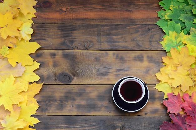 Eine tasse tee unter einem satz vergilbten gefallenen herbstlaubs