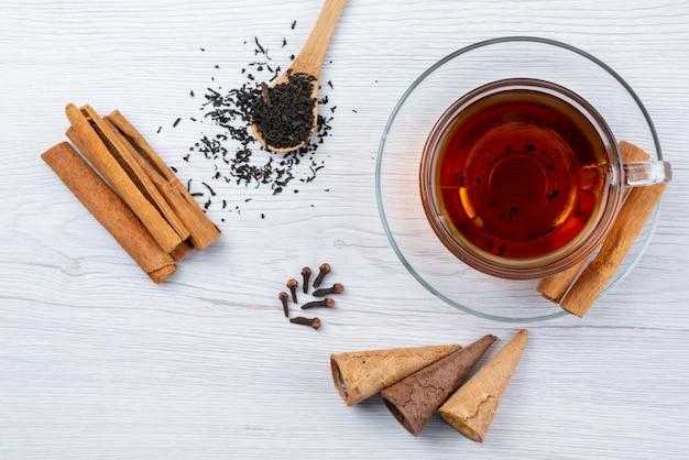 Eine tasse tee von oben mit hörnern, frischem tee und zimt auf weißem frühstücksdesserttee