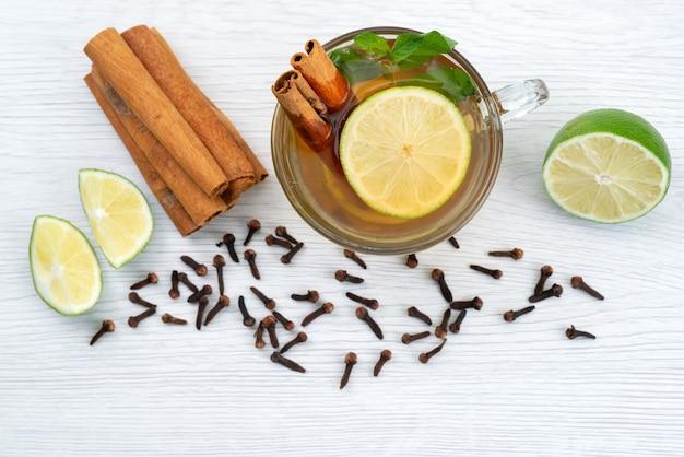 Eine tasse tee von oben mit zitronenminze und zimt auf weißem tee-dessert-bonbon